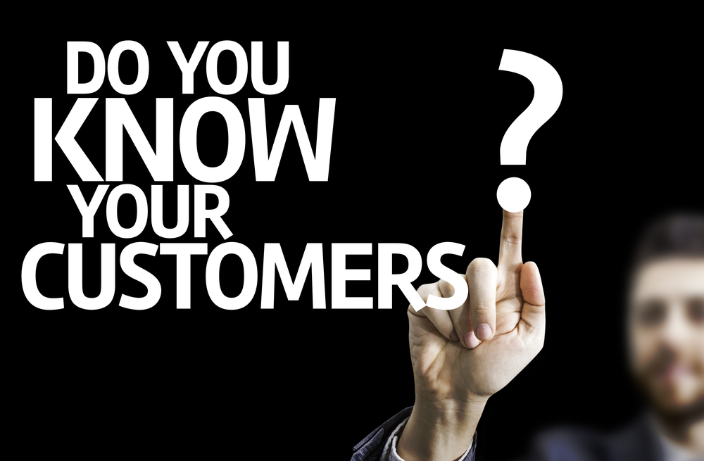 Business man pointing to black board with text Do you Know your Customers?