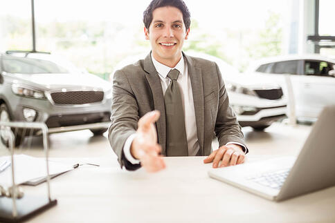 Smiling salesman ready to shake hand at new car showroom